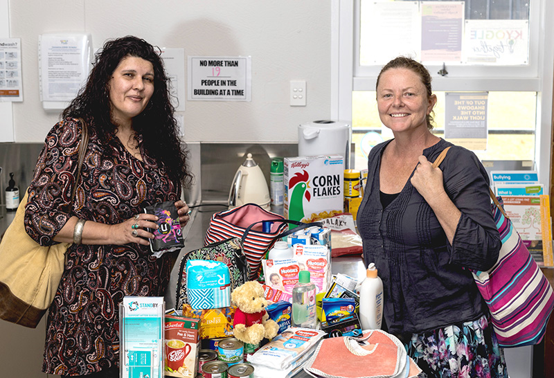 Maree and Sharyn stand smiling on either side of a collection of personal care items, food items and baby products etc
